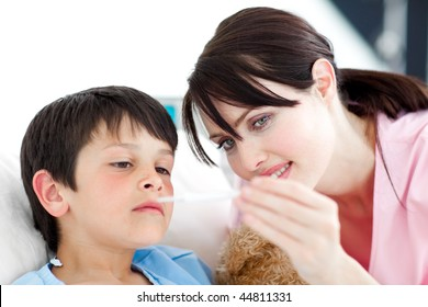 Attentive nurse and his patient looking at a thermometer in a hospital