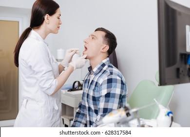 Attentive otolaryngologist doing throat exam