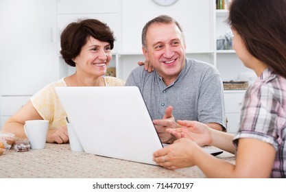 Attentive positive mature couple looking at woman showing documents on her laptop indoors. Focus on mature man