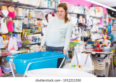 attentive pregnant female is buying bath for baby in the children's goods store