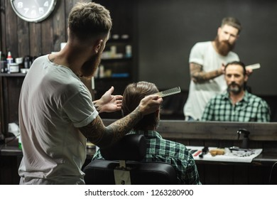Attentive professional barber holding a comb and looking at the mirror while combing the hair of his client