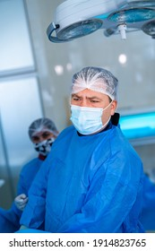 Attentive professional doctor checks operation process in modern operating room. Surgeon in blue scrubs, hat and facial mask in clinic. Portrait.