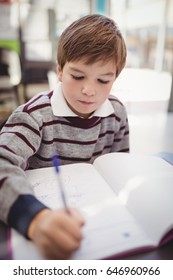 Attentive schoolboy writing in book in classroom at school