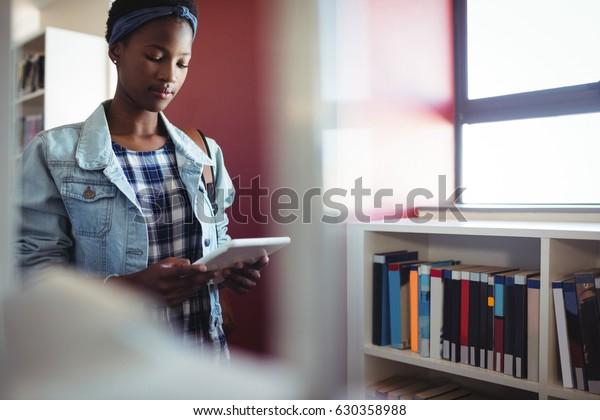 Attentive schoolgirl using digital tablet in library at school