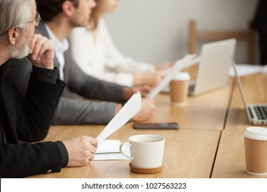 Attentive senior businessman holding documents focused on listening at group meeting, aged experienced investor, client or company executive participating training conference business seminar concept