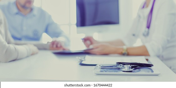 Attentive senior doctor listenint to patient in her office