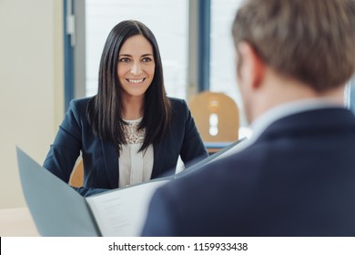 Attentive smiling young woman in a job interview waiting as the business manager reads her CV in an over the shoulder view