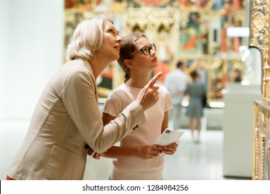 Attentive tween girl with senior woman looking with interest at gallery exposition