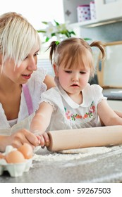 Attentive young mother baking with her daughter in the kitchen