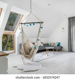 Attic living room with hammock seat, big windows, wooden floor and gray corner sofa