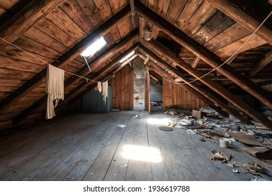 Attic room with clothesline, wooden trim and junk on the floor