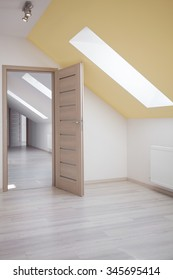 Attic room with white walls and yellow ceiling