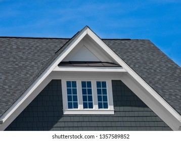 Attic three pane window on grey blue siding, gable, corbel, louver on a new construction luxury American single family home in the East Coast USA with blue sky background