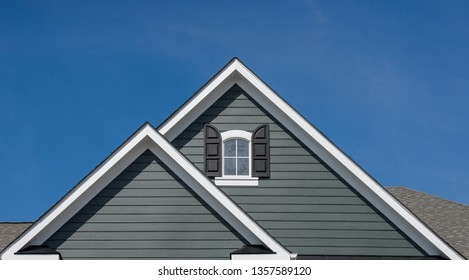 Attic window with black shutter on grey blue siding, gable, corbel, louver on a new construction luxury American single family home in the East Coast USA with blue sky background