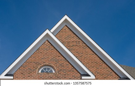 Attic window vent on brick wall, gable, corbel, louver on a new construction luxury American single family home in the East Coast USA with blue sky background