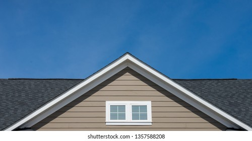 Attic window vent on brown siding, gable, corbel, louver on a new construction luxury American single family home in the East Coast USA with blue sky background
