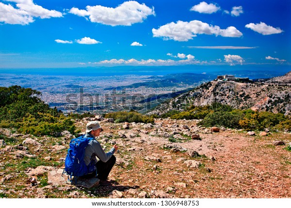 ATTICA, GREECE- April 12, 2014. Hiker enjoying the view of Athens from Parnitha mountain.