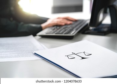Attorney with computer. Lawyer working in law firm and company. Solicitor or jurist doing paperwork. Professional business woman writing her will or legal document. Paper with scale icon on desk.