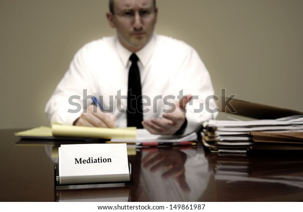 Attorney at Law sitting at desk holding pen with files with a card for Mediation