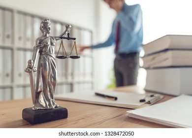 Attorney talking on mobile device in law office, selective focus on statue of Lady Justice