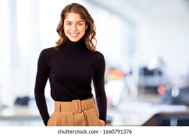 Attracive young businesswoman portrait while looking at camera and smiling. Isolated on white background.