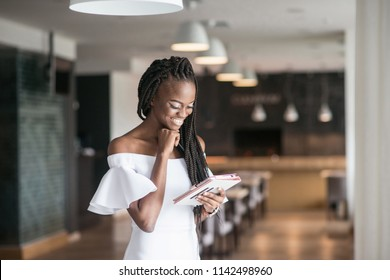Attracrive african american girl standing in a restaurant or cafe with the tablet in her hands. Dreadlocks or african braids.