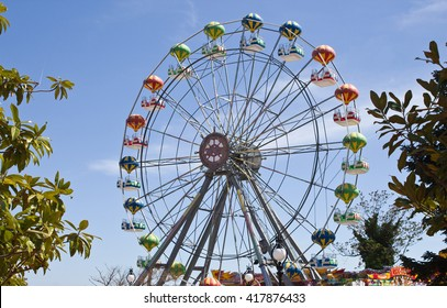 Attraction colorful ferris wheel on the background of bright blue sky