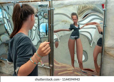 attraction, girl looking at her image in the distorted mirror in the hall of mirrors