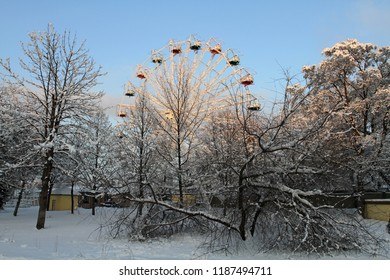 The attraction wheel in the winter park is covered with snow. Force majeure a large amount of precipitation stopped the measured course of life in the city.