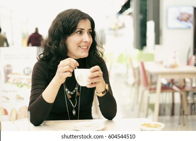 attractive 30 years old woman in bar terrace drinking coffee