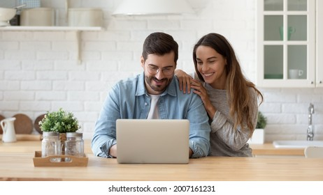 Attractive 35s couple sit at table in cozy kitchen looking at laptop screen, buying goods, tickets online, using e-commerce retail e-services feel satisfied, enjoy comfort usage of modern technology