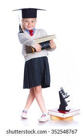 Attractive 5 year old girl in  large graduation cap with book and microscope over white background