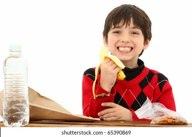 Attractive 7 year old french american boy in school desk over white eating a sack lunch or snack.