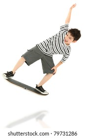 Attractive 8 year old boy playing on video game skateboard controller jumping over white background.