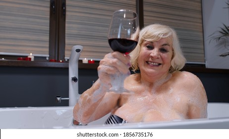 Attractive active senior woman lying in warm bath with bubbles, enjoying relaxation, drinking red wine. Cheerful happy elderly grandmother at luxury home bathroom in a romantic setting with candles