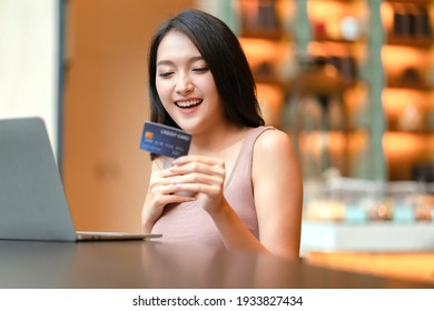 attractive adult asian female happiness shopping online with laptop hand hold credit card and smartphone for purchase product with background of cafe restaurant business ideas concept