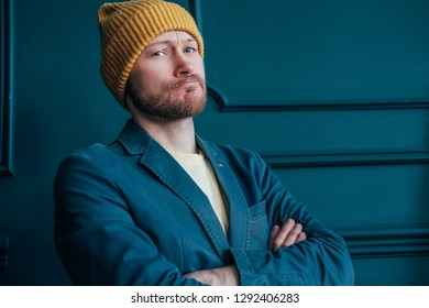 Attractive adult bearded angry man hipster in yellow hat looks at camera  and furrowed his brows ec944ef84ddf