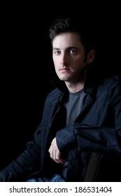 Attractive adult brunette male model against black background
