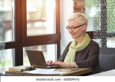 Attractive adult business woman looking in the laptop screen and smiling while sitting at her working place in office. Working day.