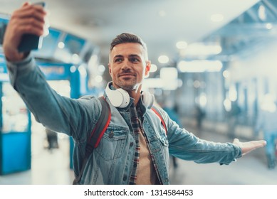 Attractive adult man standing in airport terminal. He making selfie on front camera of telephone and showing his friends where he is