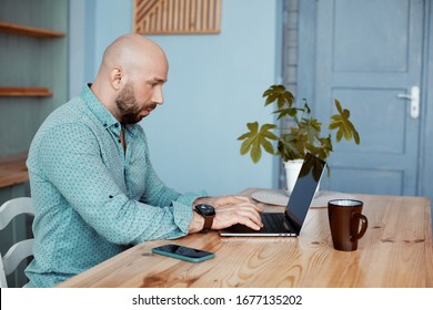 Attractive adult man working on a computer during morning coffee. Business, work, work at home, quarantine during the epidemic of the coronavirus COVID-19