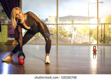 Attractive adult woman in 30s doing kettlebell exercises in zumba club. Toned image.