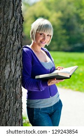 attractive adult woman with book outside