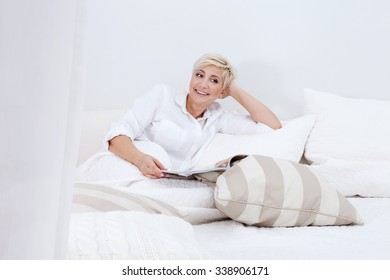 Attractive adult woman relaxing in bed, reading newspaper. Home interior.