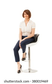 Attractive adult woman sitting on chair and looking at camera. White background, studio shot. Isolated.