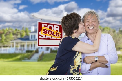 Attractive Affectionate Senior Chinese Couple In Front of Beautiful House and Sold For Sale Real Estate Sign.