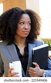 Attractive African American Business Professional Business Woman Holding Folder and Coffee Cup