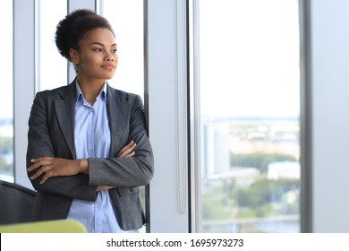 Attractive african american business woman smiling while standing in the office.