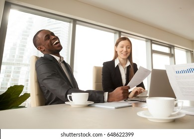 Attractive African american businessman with beautiful smile laughing, multi-ethnic group meeting, friendly atmosphere during discussion, business people joking having fun sitting at conference table
