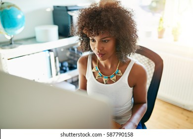 Attractive African American businesswoman sitting at her computer in a high key office working on a large desktop monitor